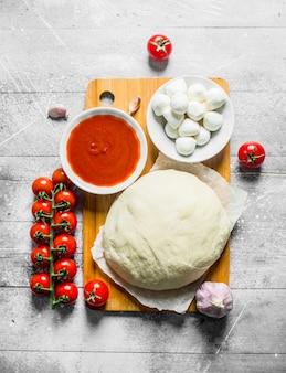 Deeg met verschillende ingrediënten voor zelfgemaakte pizza op witte rustieke tafel