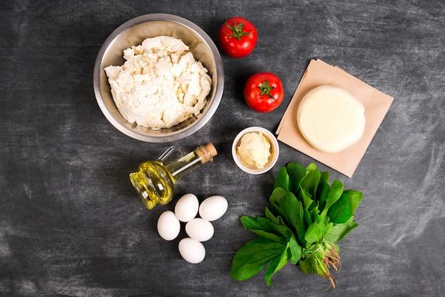Deeg, olie, kaas, tomaten, eieren, groenen over grijze houten oppervlak