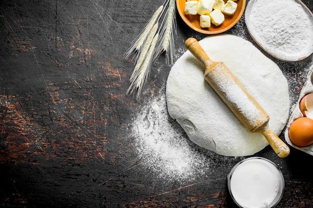 Deeg oppervlak. deeg met boter, melk en bloem in kommen. op rustieke ondergrond