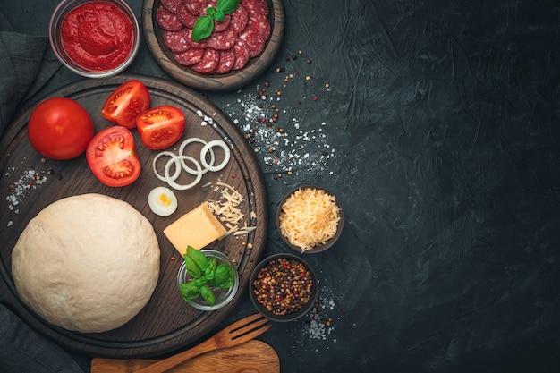 Deeg, salami, tomaten, kaas, basilicum en kruiden op een zwarte achtergrond. ingrediënten voor pizza. koken concept.