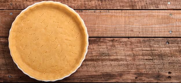 Deeg voor het bakken van quiche, taart of taart in keramische bakvorm klaar voor bakken op keukenhanddoek over oude rustieke plank houten achtergrond. bovenaanzicht, kopieer ruimte. concept zelfgemaakte bakken voor vakantie. banier.