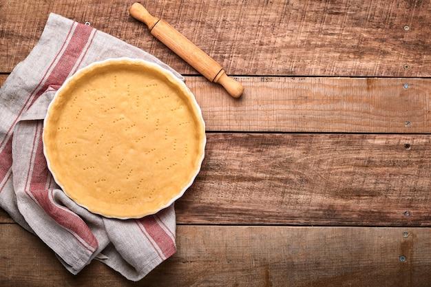 Deeg voor het bakken van quiche, taart of taart in keramische bakvorm klaar voor bakken op keukenhanddoek over oude rustieke plank houten achtergrond. bovenaanzicht, kopieer ruimte. concept zelfgemaakte bakken voor vakantie.