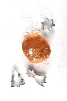 Deeg voor het bereiden van zelfgemaakte peperkoek kerstkoekjes naast de uitsteekvormpjes