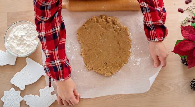 Deeg voor ontbijtkoek op bakpapier, dat met de hand wordt rechtgetrokken. kerst bakken.