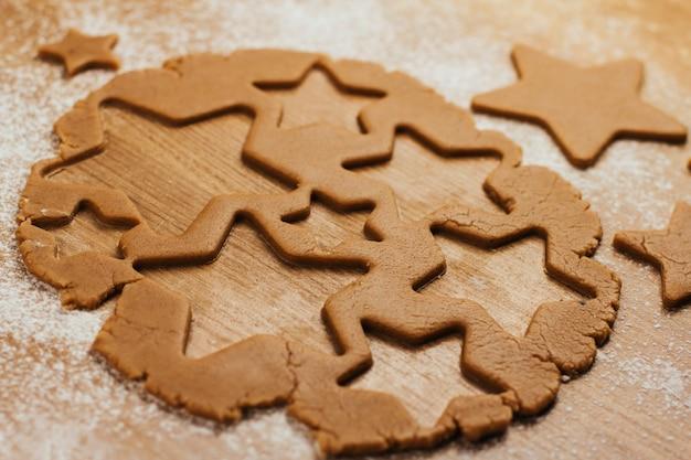 Deeg voor peperkoekkoekjes op een met bloem bestrooide tafel. koekjes snijden in de vorm van sterren.