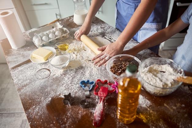 Deeg wordt uitgerold op een rommelige keukentafel