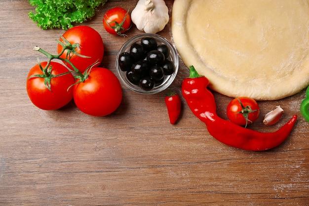 Deegbasis en ingrediënten voor pizza, op tafel