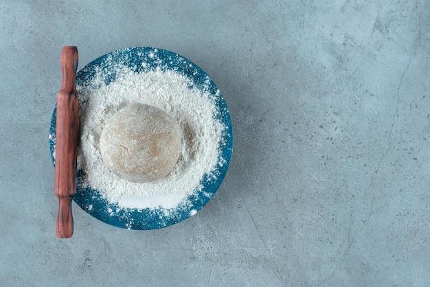 Deegbroodje met bloem op blauw bord met deegroller.