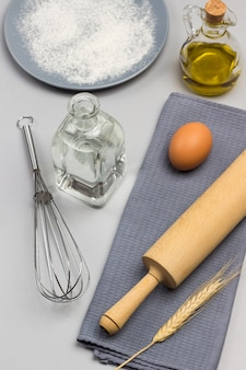 Deegrol, ei en aartje van tarwe op grijs servet. metalen garde, twee flessen water en olie. grijze plaat met bloem. bovenaanzicht.