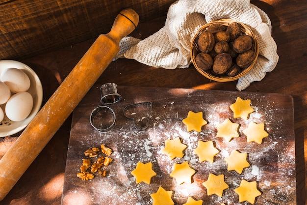 Deegroller en koekjesmessen in de buurt van rauwe koekjes en ingrediënten