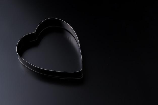 Deegsnijder in vorm van hart op een donkere achtergrond met exemplaarruimte. valentijnsdag achtergrond