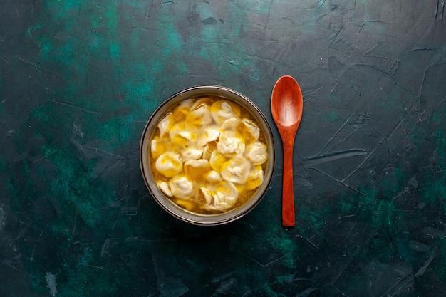 Deegsoep van het bovenaanzicht met gehakt in het deeg op het donkerblauwe bureau ingrediënt soep eten maaltijd deeg schotel dinersaus