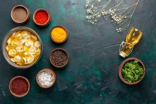 Deegsoep van het bovenaanzicht met verschillende kruiden en olijfolie op de donkerblauwe achtergrondingrediëntsoep, voedselmaaltijddeeg, dinersaus