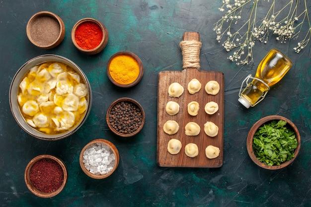Deegsoep van het bovenaanzicht met verschillende kruiden en olijfolie op donkerblauwe oppervlakte ingrediënten soep eten maaltijd deeg dinersaus