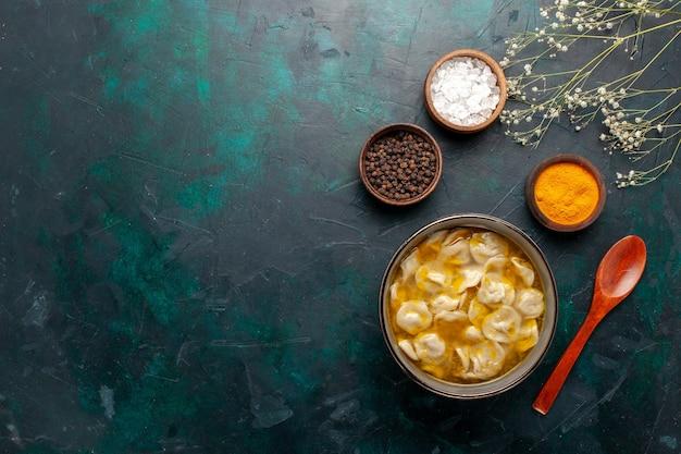 Deegsoep van het bovenaanzicht met verschillende kruiden op donkerblauwe bureauingrediënten soep, maaltijd, deeg, dinersaus