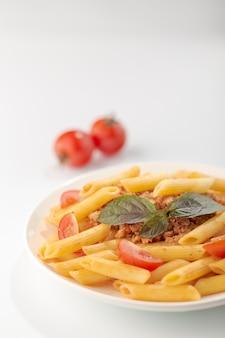 Deegwaren fettuccine bolognese met tomatensaus en basilicum in witte schotel op wit