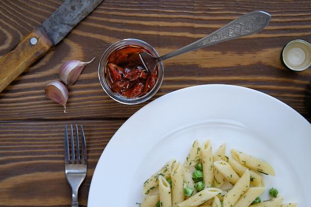Deegwaren met de groene erwtenknoflook en dille van de pestosaus op een plaat houten lijst. het uitzicht vanaf de top. italiaanse keuken. vegetarisch veganistisch eten. goede gezonde voeding. gedroogde tomaten in olijfolie.