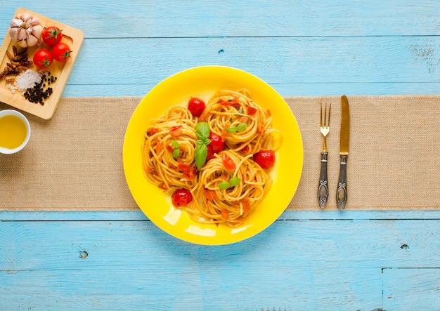Deegwaren met tomatensaus en andere componenten op een lichtblauwe houten vrije ruimte als achtergrond voor tekst.