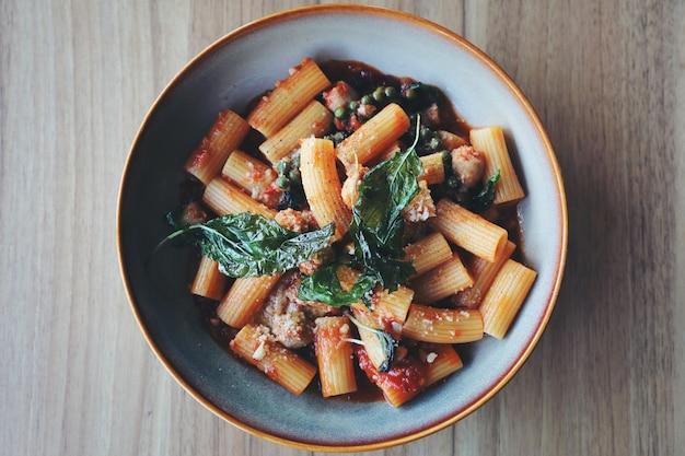 Deegwaren met worst in tomatensaus op houten achtergrond, italiaans voedsel