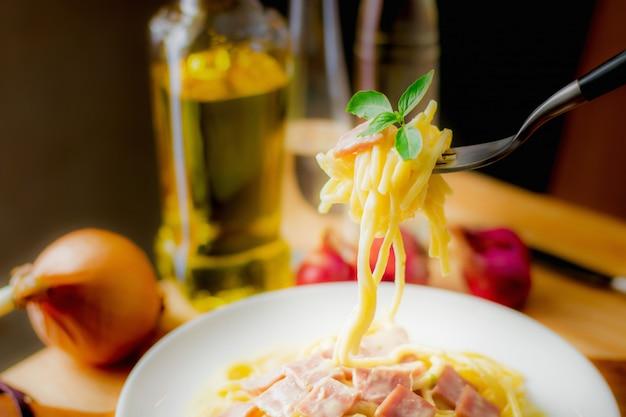 Deegwaren, spaghetticarbonara met ham in de witte plaat op houten lijst