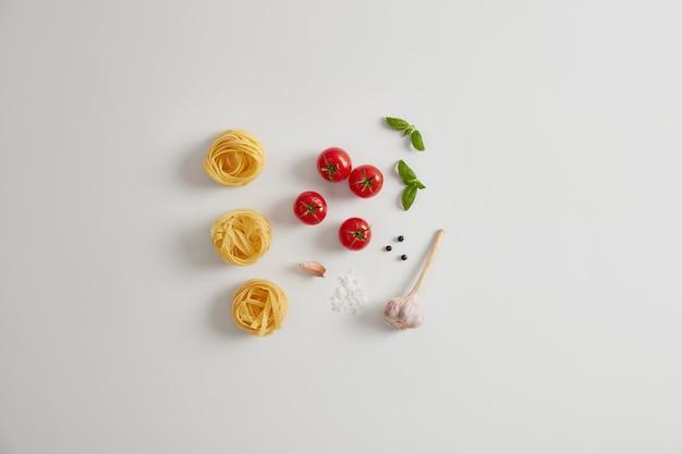 Deegwareningrediënten op witte achtergrond. rode kerstomaatjes, basilicum, knoflook, peperkorrels, ongekookte pastanesten voor het bereiden van smakelijke gerechten. italiaanse keuken concept. gezond vegetarisch dieet. plat leggen