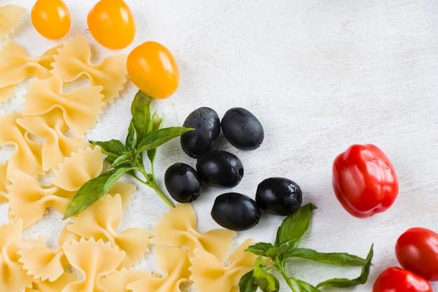 Deegwareningrediënten, ruwe deegwaren, kerstomaatjes, olijven en basilicumbladeren op de witte achtergrond