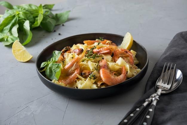Deegwarenreginelle met zeevruchten, garnalen, mosselen op grijze steenlijst, sluiten omhoog. traditioneel gerecht in het italiaanse restaurant.