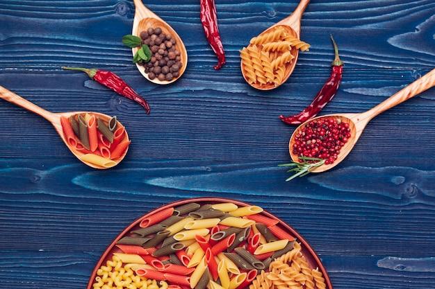 Deegwarenspaghetti, groenten en kruiden, op houten lijst