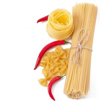 Deegwarenspaghetti, groenten, kruiden die op wit worden geïsoleerd