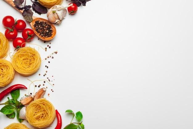 Deegwarenspaghetti met ingrediënten voor het koken van deegwaren op wit