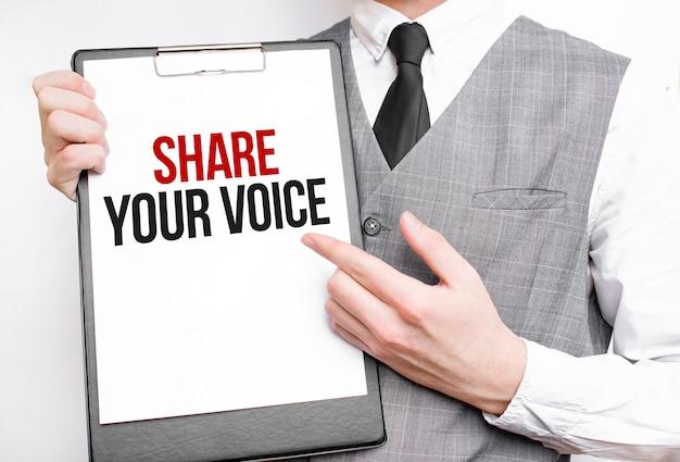 Deel uw stem inscriptie op een notitieboekje in de handen van een zakenman op een grijze achtergrond