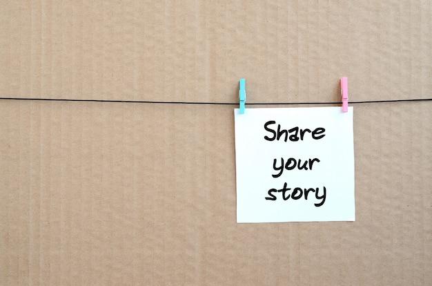 Deel uw verhaal. opmerking staat geschreven op een witte sticker die blijft hangen