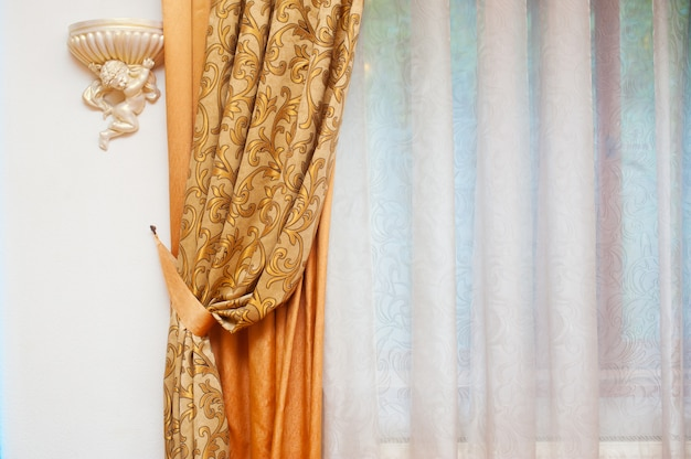 Deel van prachtig gedrapeerde gordijn en muur met patronen
