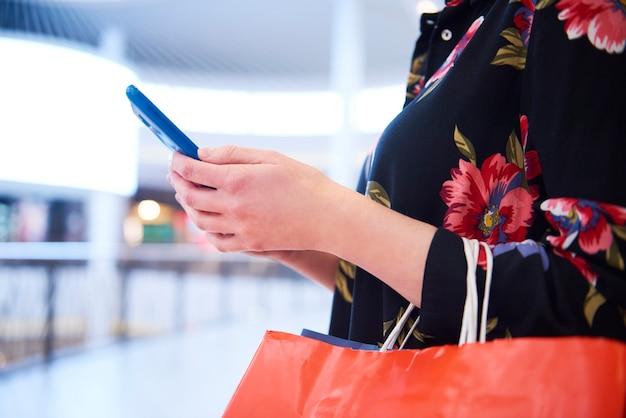 Deel van vrouw die mobiele telefoon gebruikt tijdens het winkelen