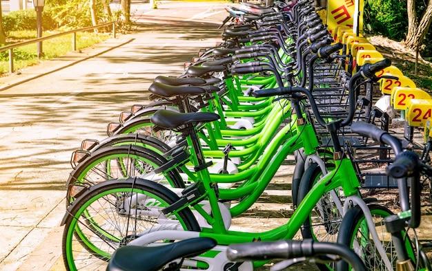 Deelfietssystemen. fiets te huur bedrijf. fiets voor stadstour bij fietsenstalling. milieuvriendelijk vervoer. stedelijke economie openbaar vervoer. fietsstation in het park. gezonde levensstijl.