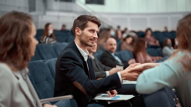 Deelnemers aan het zakelijke seminar begroeten elkaar met een handdruk