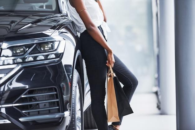Deeltjesmening van jonge afro-amerikaanse vrouw in glazen staat in autosalon in de buurt van voertuig met pakket in handen.