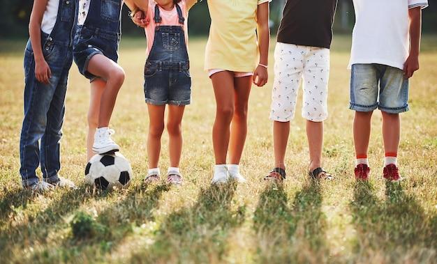 Deeltjesweergave van sportieve kinderen met voetbal staat samen in het veld op een zonnige dag.