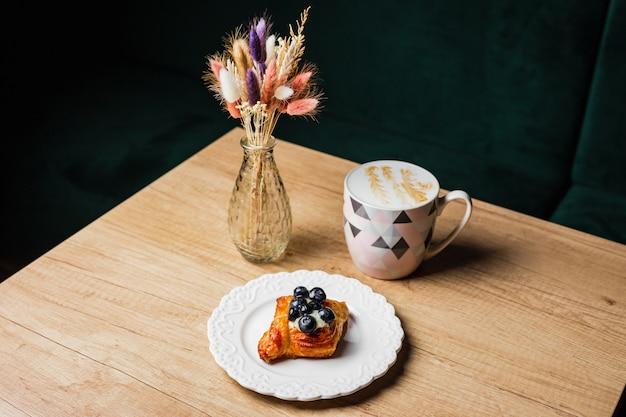 Deens gebak met vla en moeras bosbes op een witte plaat, een mok van platte witte koffie en bloemen in een vaas