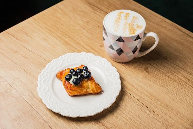 Deens gebak met vla en moeras bosbes op een witte plaat en een mok van platte witte koffie