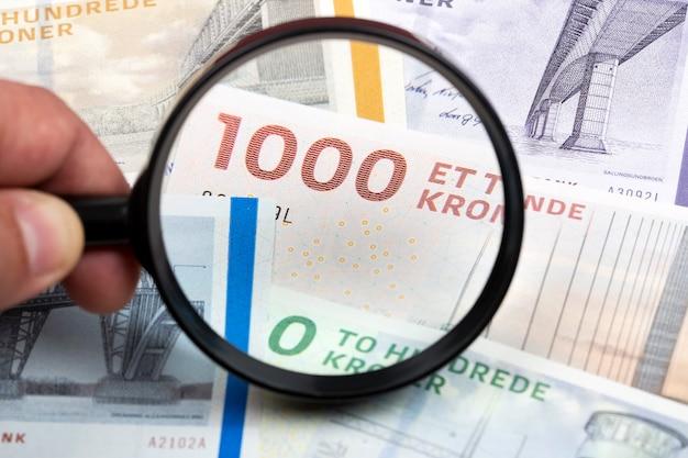 Deens geld in een vergrootglas een bedrijfsachtergrond