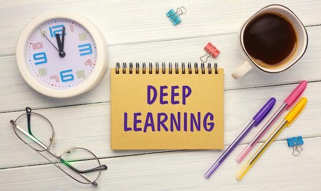 Deep learning - een inscriptie op een notitieboekje op tafel met een klok, koffie en glazen