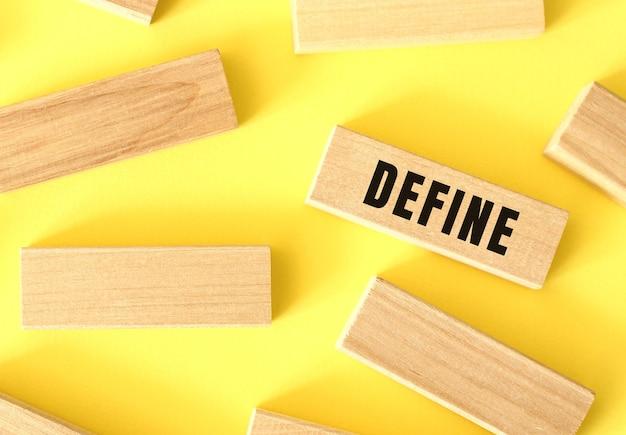 Define tekst geschreven op een houten blokken op een gele achtergrond.