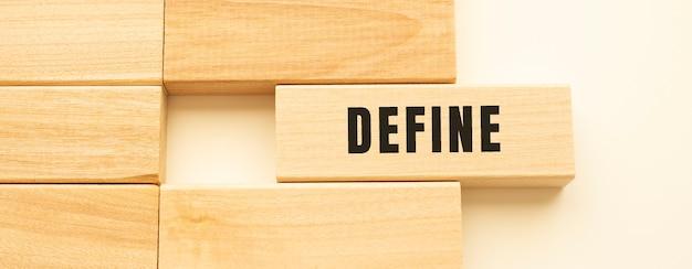 Define tekst op een strook hout die op een witte tafel ligt.