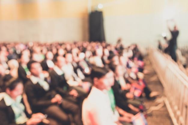 Defocus van de spreker op het podium en het geven van praten op zakelijke bijeenkomst.