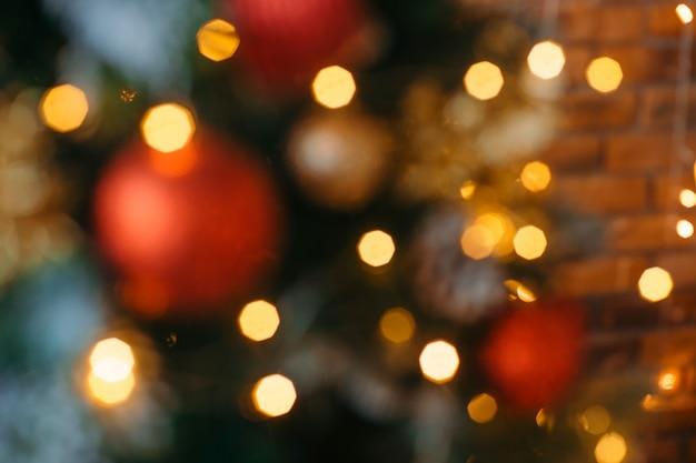 Defocus versierde kerstboomclose-up. rode en gouden ballen en verlichte slinger met zaklampen