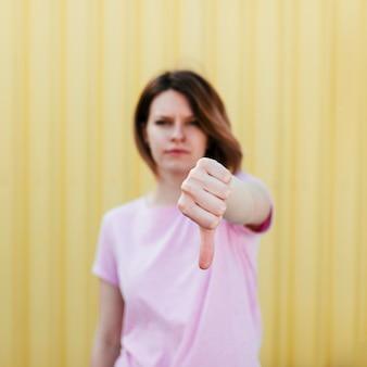 Defocused jonge vrouw die duim neer tegen gele achtergrond toont