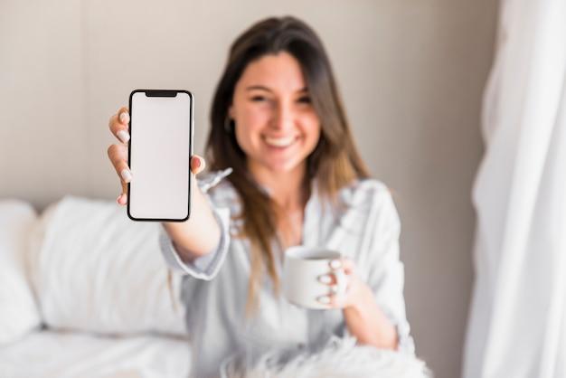Defocused jonge vrouw die witte lege het scherm mobiele telefoon toont