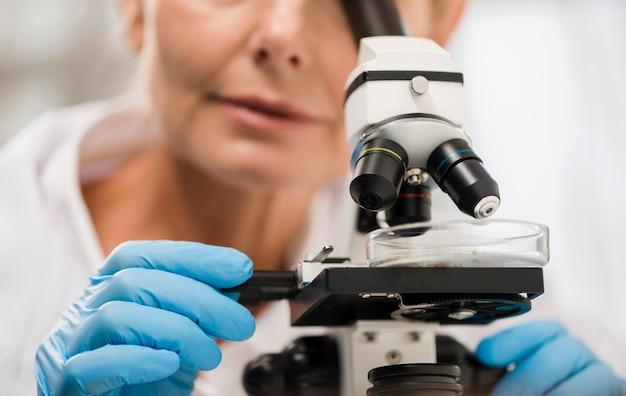 Defocused vrouwelijke wetenschapper die door microscoop kijkt