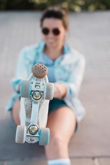 Defocussed jonge vrouw die voet met rolschaats toont